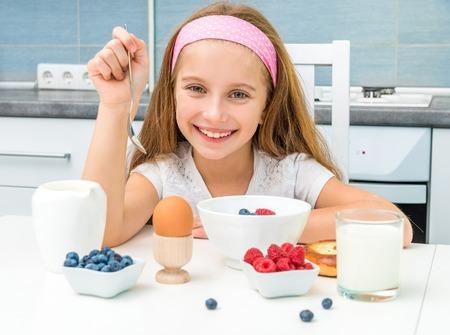 smiling little girl having breakfast
