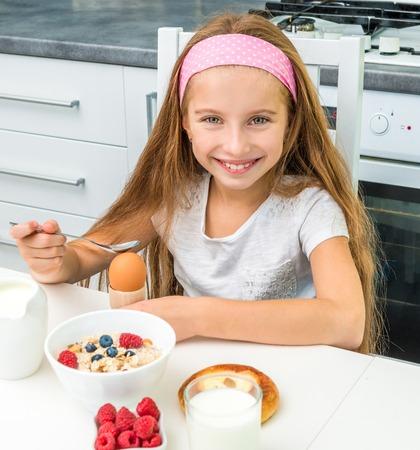 niña comiendo: sonriente niña comiendo huevo para el desayuno Foto de archivo