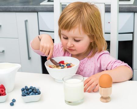 niños desayunando: niño pequeño comer muesli para el desayuno