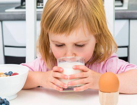 niños desayunando: niño tomar leche mientras que el desayuno