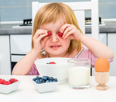 child smile: little child playing raspberry while breakfast Stock Photo