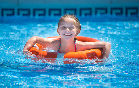cute girl with long hair: happy little girl swims with a lifeline in the pool in  summer