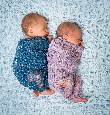 newborns: newborn twins - a boy and a girl sleeping on a blue blanket Stock Photo