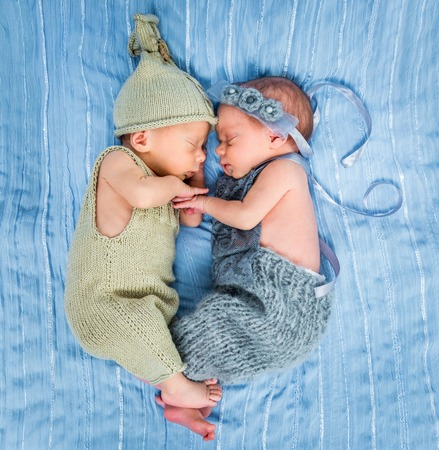 baby on hands: newborn twins - a boy and a girl sleeping on a blue blanket Stock Photo