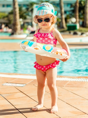 little cute girl near the pool with a circle for swimming Stock Photo