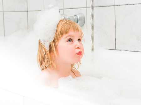 bath: cute two year old baby bathes in a bath with foam closeup Stock Photo