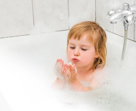 baby bath: cute two year old baby bathes in a bath with foam closeup Stock Photo