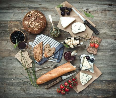 pan y vino: Alimentos francés sobre un fondo de madera. Diferentes tipos de queso, el vino y otros ingredientes en una mesa de madera Foto de archivo