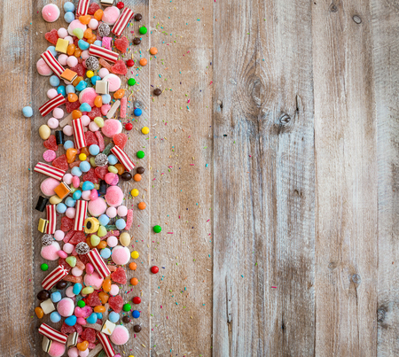 candy background: variety of candies on a wooden background with space for text