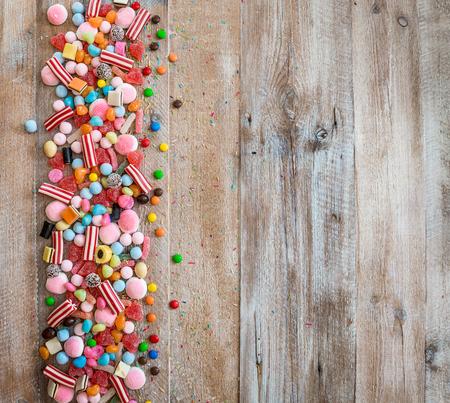 Vielzahl von Süßigkeiten auf einem hölzernen Hintergrund mit Platz für Text
