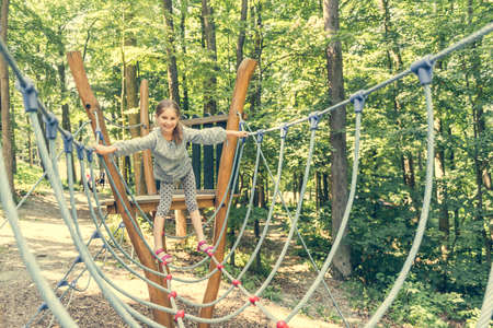 rope ladder: happy little girl in a rope park on the wood background