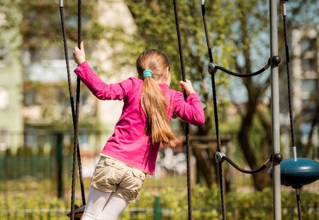 jungle gym: cute happy little girl on outdoor playground