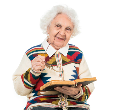 the great grandmother: elderly woman flipping an old book isoalted on white background Stock Photo