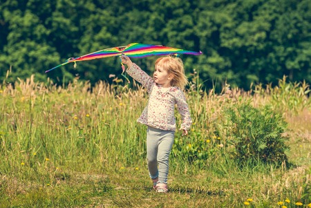 enfant qui joue: little cute girl flying a kite in a meadow on a sunny day. close-up