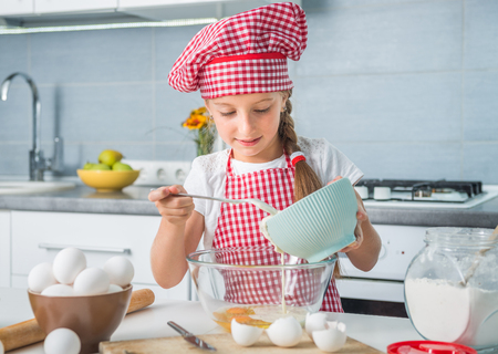 home cooking: cute little girl preparing a dough with eggs and cream