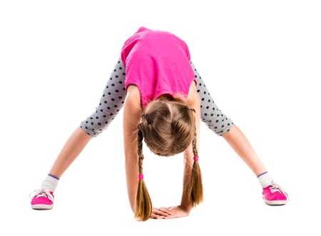 doing: cute little girl stretching isolated on white background Stock Photo