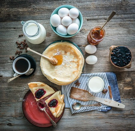 prepared pancakes and coffee among ingredients on wooden background Foto de archivo