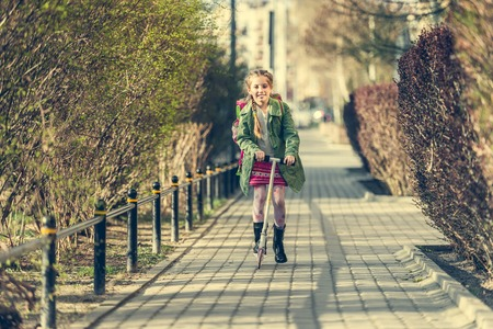 autmn: girl returning from school on a scooter