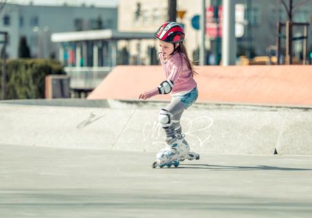 niño en patines: Niña bonita en patines en casco en un parque Foto de archivo