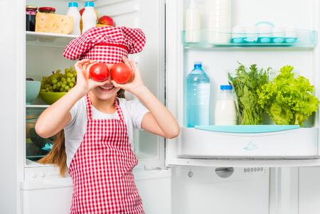 eyes opened: little cook girl holdin tomatoes like eyes near opened fridge Stock Photo