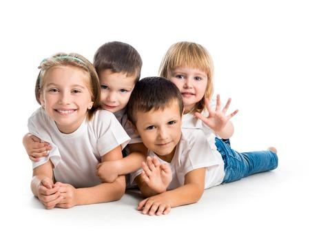 niños sonriendo: niños sonrientes que mienten en el suelo aislado en el fondo blanco