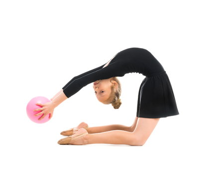 limber: little gymnast doing exercise with ball isolated on white background
