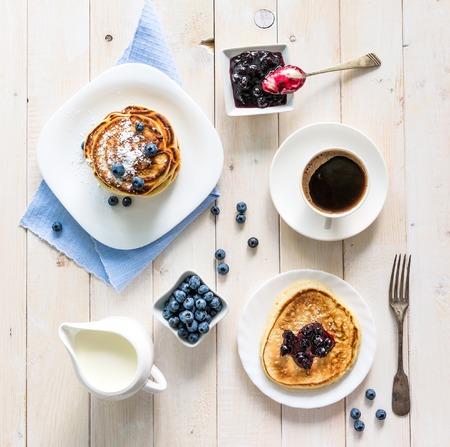 견해: 나무 배경에 블루 베리와 커피와 팬케이크. 평면도