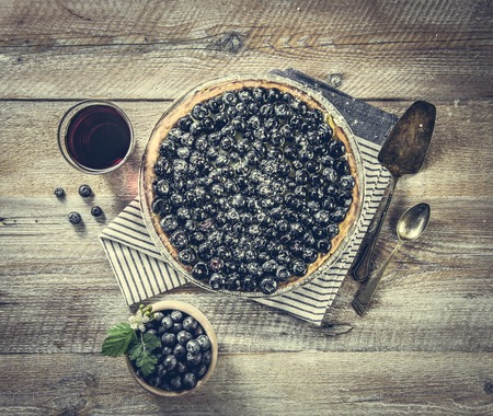 angle: Tart with blueberries and juice on a wooden background. top view