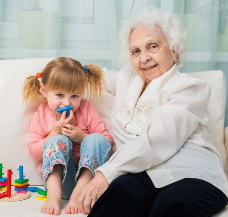 the great grandmother: little girl with grandmother sitting on a sofa with toys