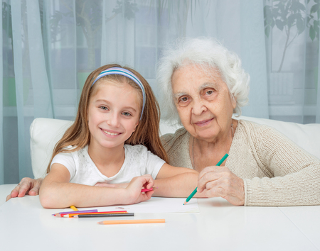 grandkid: portrait of little girl with grandmother drawing with pencils