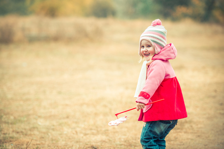 autmn: little smiling girl on autumn landscape with pinwheel toy Stock Photo