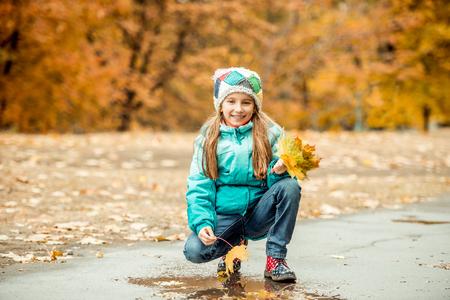 en cuclillas: prettypretty niña en cuclillas con las hojas en la mano en el paisaje de otoño