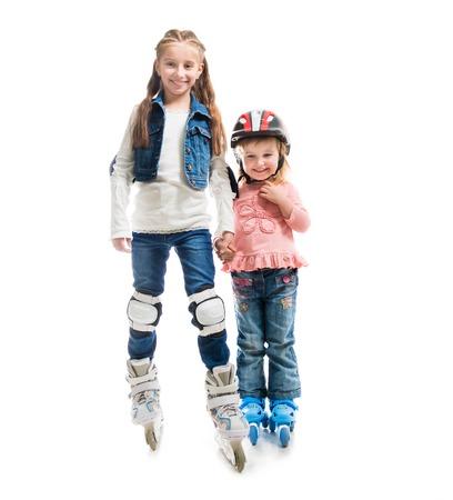 rollerskates: two smiling little girls on rollerskates isolated on white background