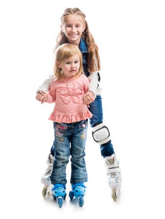 rollerskater: two smiling little girls on rollerskates isolated on white background