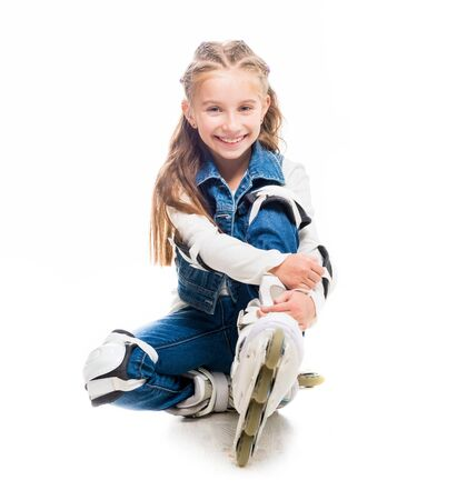 rollerskater: cute teenager girl on rollerskates sitting on the floor isolated on white background