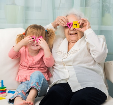 the great grandmother: grandmother with granddaughter playing toys sitting on sofa Stock Photo