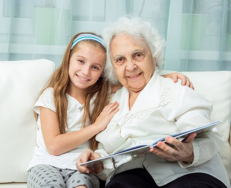 grandkid: elderly woman with granddaughter with book on sofa
