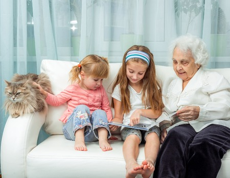 grandmother and children: elderly woman with granddaughters reading book on sofa with cat Stock Photo