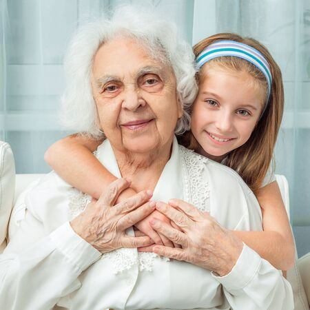 the great grandmother: smiling little girl embracing grandmother