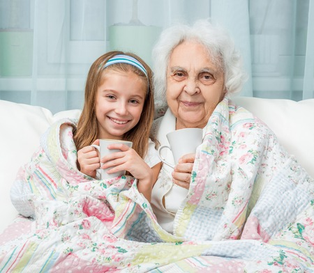 great grandmother: grandmother and granddaughter drink tea covered with blanket