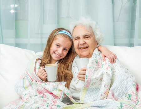 the great grandmother: grandmother and granddaughter drink tea covered with blanket