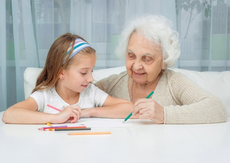 the great grandmother: portrait of little girl with grandmother drawing with pencils