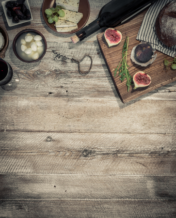lunch table: cheeses and brown bread on wooden table with text space
