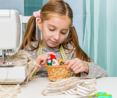 maquinas de coser: little seamstress sitting at the table with threads in basket and sewing machine