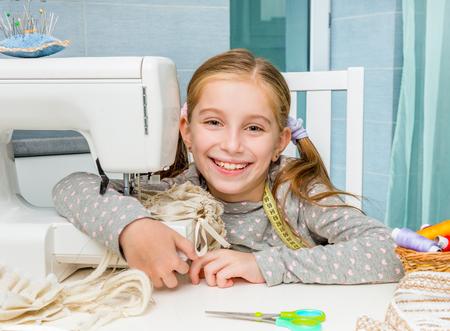 cinta metrica: una sonrisa de niña en la mesa con la máquina de coser que mira la cámara Foto de archivo
