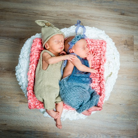baby on hands: newborn twins - a boy and a girl sleeping in a basket
