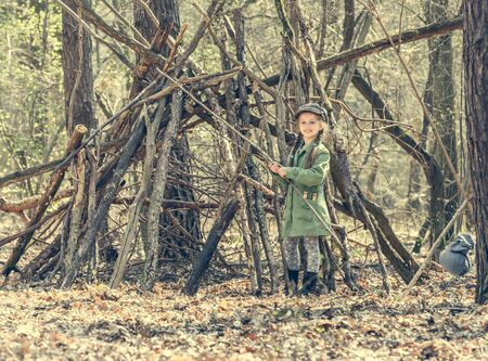 ittle: ittle cute girl builds a hut in the woods. Photo in retro style Stock Photo