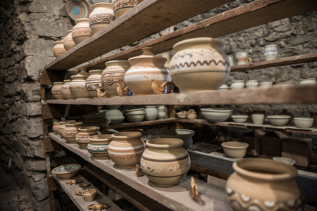 clay craft: shelves with Ukrainian ceramics in potter workshop