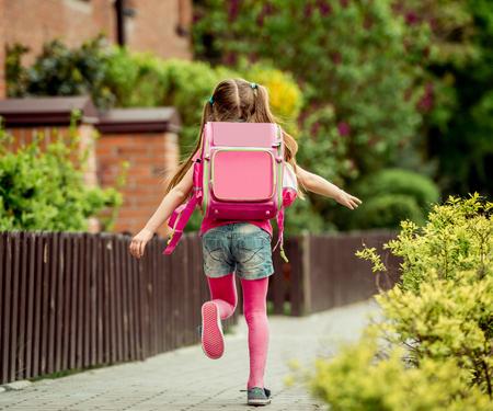 kleines Mädchen mit einem Rucksack in die Schule laufen. Rückansicht Standard-Bild