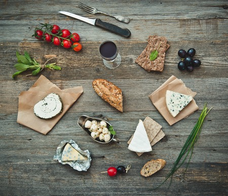 life loaf: French food on a wooden background. Different types of cheese, wine and other ingredients on a wooden table Stock Photo